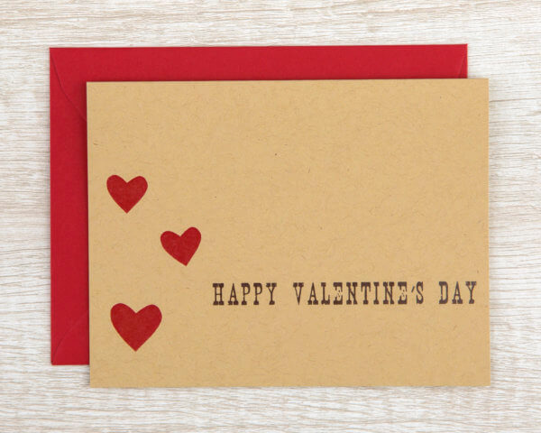 """Rustic Valentine's Day card with red hearts on brown paper that reads """"Happy Valentine's Day"""" with a red envelope"""