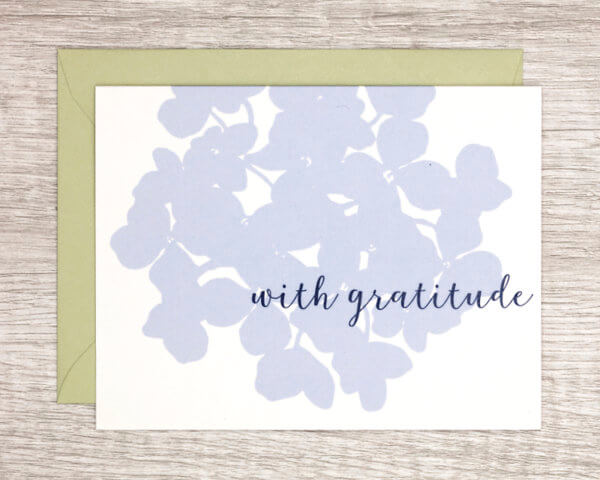 """White thank you card with a large, pale blue hydrangea that reads """"With gratitude"""" with a pale green envelope"""