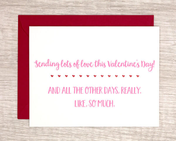 """Modern quirky Valentine's day card for friends and family that reads """"Sending lots of love this Valentine's Day! And all the other days, really, like, so much."""" in pink with red hearts and a red envelope."""