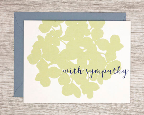 """White condolences card with a large, pale green hydrangea that reads """"With sympathy"""" with a blue envelope"""