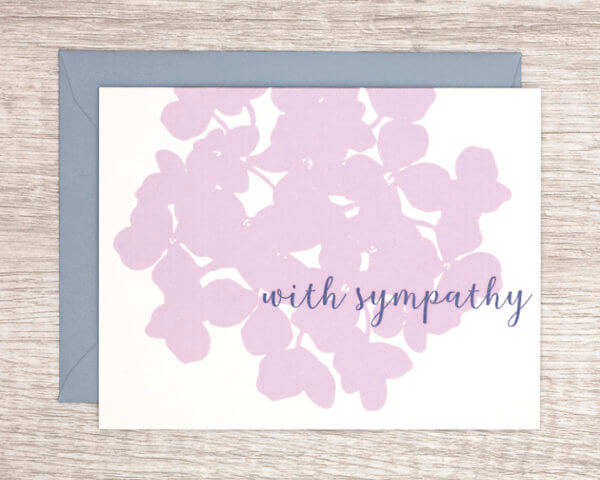"""White condolences card with a large, pale pink hydrangea that reads """"With sympathy"""" with a blue envelope"""