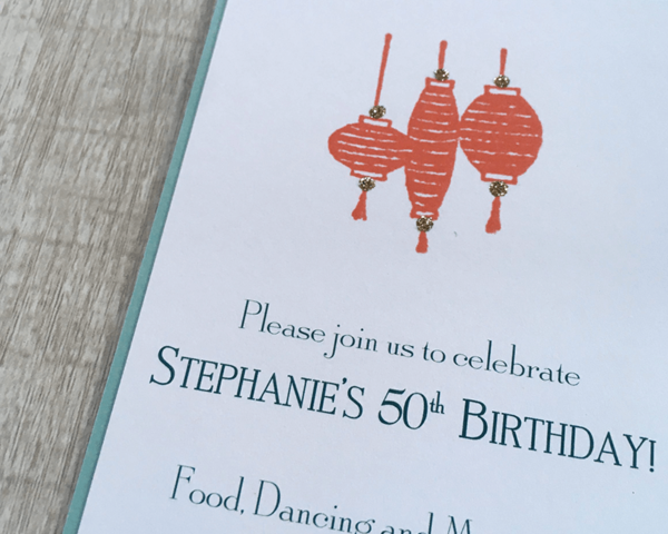 A custom birthday invitation with sparkly red paper lanterns