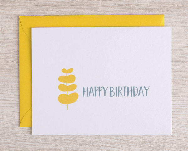 """A birthday card that reads """"Happy birthday"""" in blue with a yellow branch of leaves and a matching yellow envelope"""