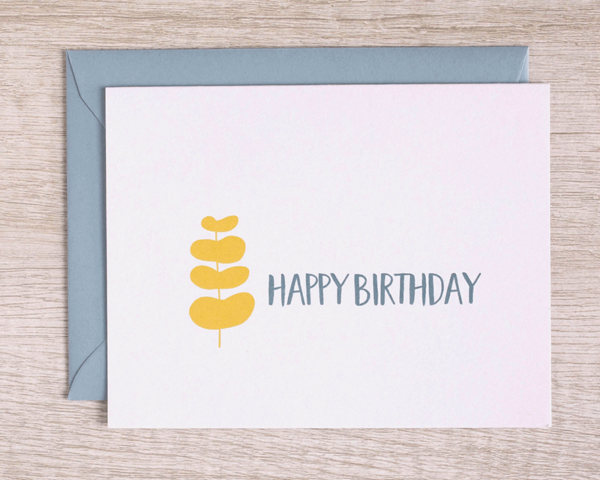 """A birthday card that reads """"Happy birthday"""" in blue with a yellow branch of leaves and a matching blue envelope"""