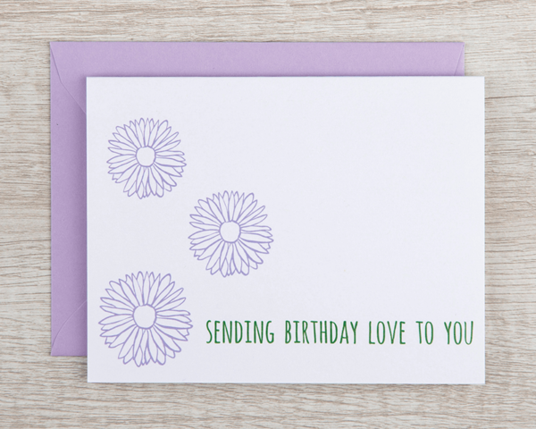 """A feminine birthday card that reads """"sending brithday love to you"""" in green with lilac blossoms"""