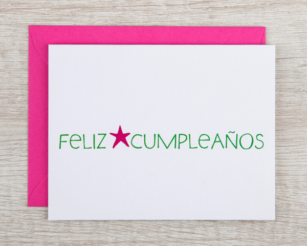 """A Spanish birthday cards that reads """"feliz cumpleaños"""" in green with a hot pink star"""