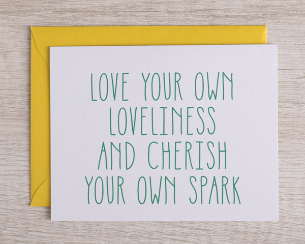 """A friendly greeting card that reads """"Love your own loveliness and cherish your own spark"""" in green with a complementary yellow envelope"""