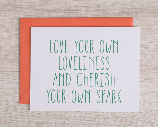 """A friendly greeting card that reads """"Love your own loveliness and cherish your own spark"""" in green with a complementary orange envelope"""