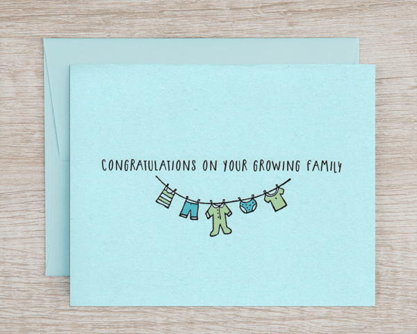 """A blue baby announcement card that reads """"congratulations omn your growing family"""" with a clothesline holding baby clothes in green and blue"""