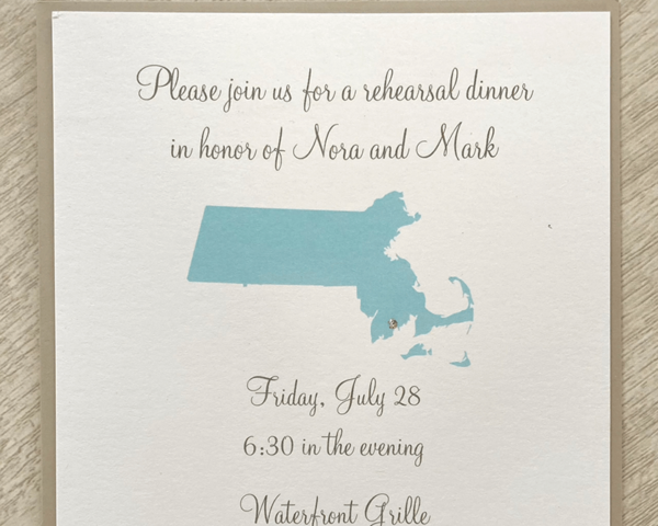 A custom wedding rehearsal dinner invitation with the state of Massachusetts on it and a small sparkly gem to mark the location