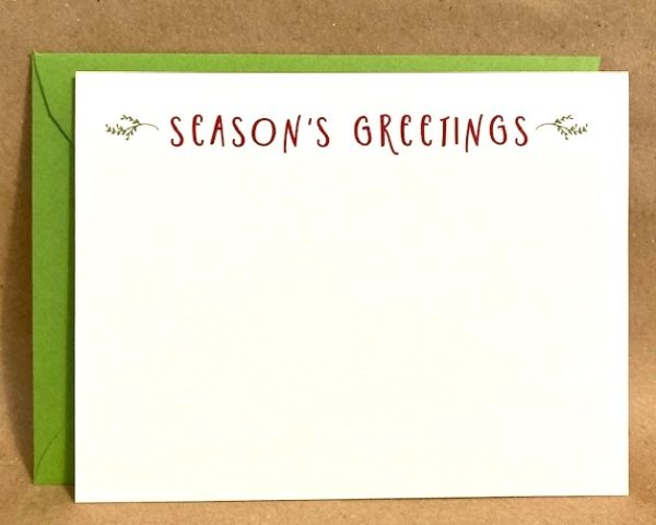 """A white holiday card that says """"Season's Greetings"""" in red with forest green branches with a matching green envelope"""