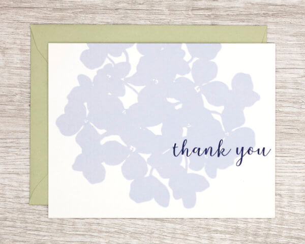"""White gratitude card with a large, pale blue hydrangea that reads """"Thank you"""" with a pale green envelope"""