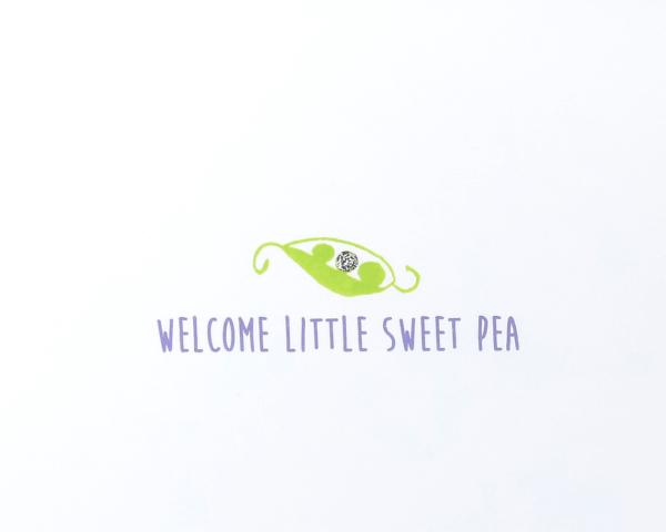 "White baby congratulations card with a stylized green peapod that reads ""welcome little sweet pea"" in purple"