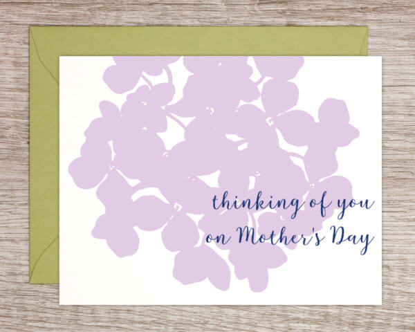 """Mother's Day greeting card that reads """"thinking of you on Mother's Day"""" with a purple hydrangea print in the background and a green envelope"""