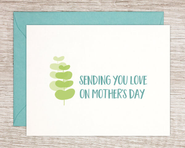 """White Mother's Day greeting card for any mom with a green natural leaf pattern that reads """"sending you love on Mother's Day"""" in blue with a blue envelope"""