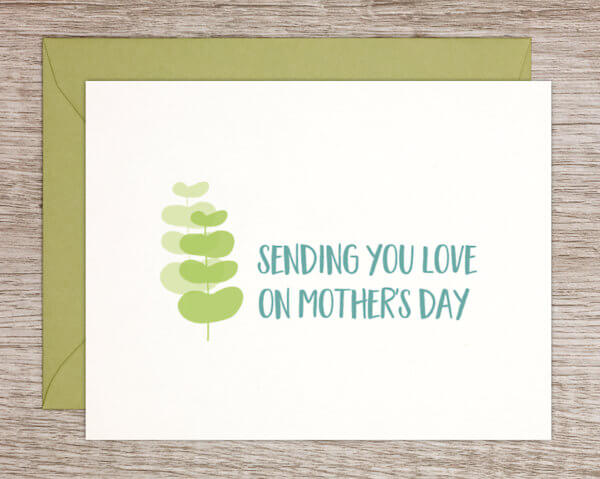 "White Mother's Day greeting card for any mom with a green natural leaf pattern that reads ""sending you love on Mother's Day"" in blue with a green envelope"