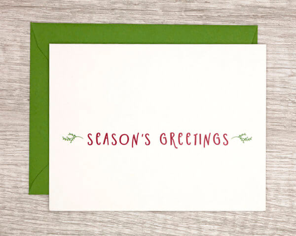 """Simple winter holiday and christmas card that reads """"season's greetings"""" in red with a green envelope"""