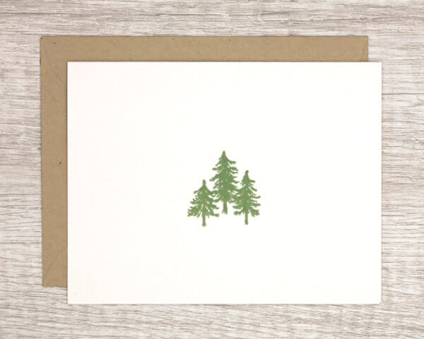 Simple white winter holiday card with a stand of three evergreen trees and a brown paper envelope