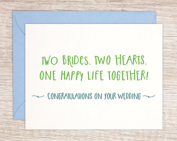 """LGBTQ+ pride greeting card that reads """"Two brides. Two hearts. One happy life together!"""" in green and """"Congratulations on your wedding"""" in blue"""""""