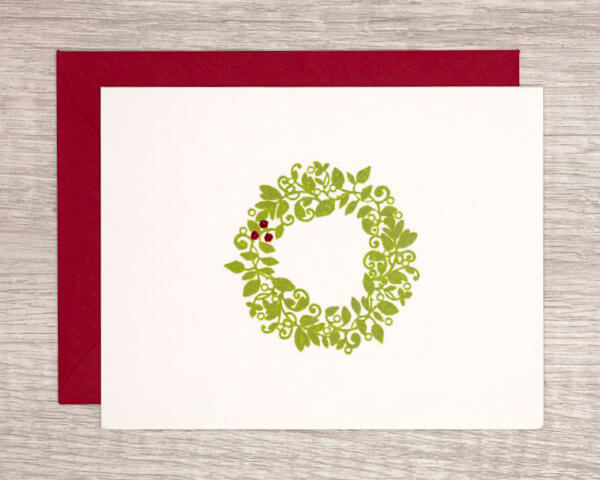 Modern minimal winter holiday card that features a green wreath with sparkly red berries with a red envelope