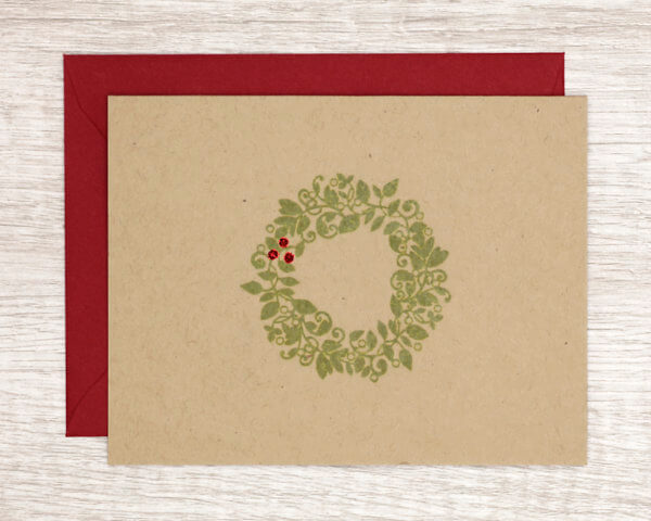 Rustic winter holiday card that features a green wreath with sparkly red berries on brown paper with a red envelope
